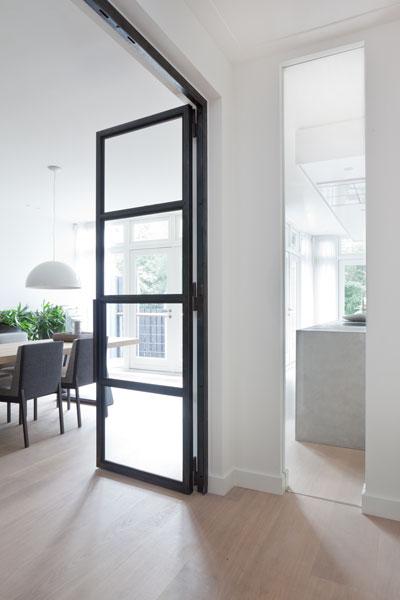 Doorkijk naar de woonkamer, stalen deur, houten vloer, stadsvilla, Remy Meijers