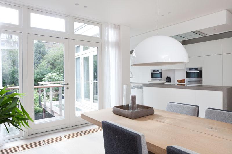 Eetkamer met zicht op de tuin, grote ramen, houten tafel, Stadsvilla, Remy Meijers