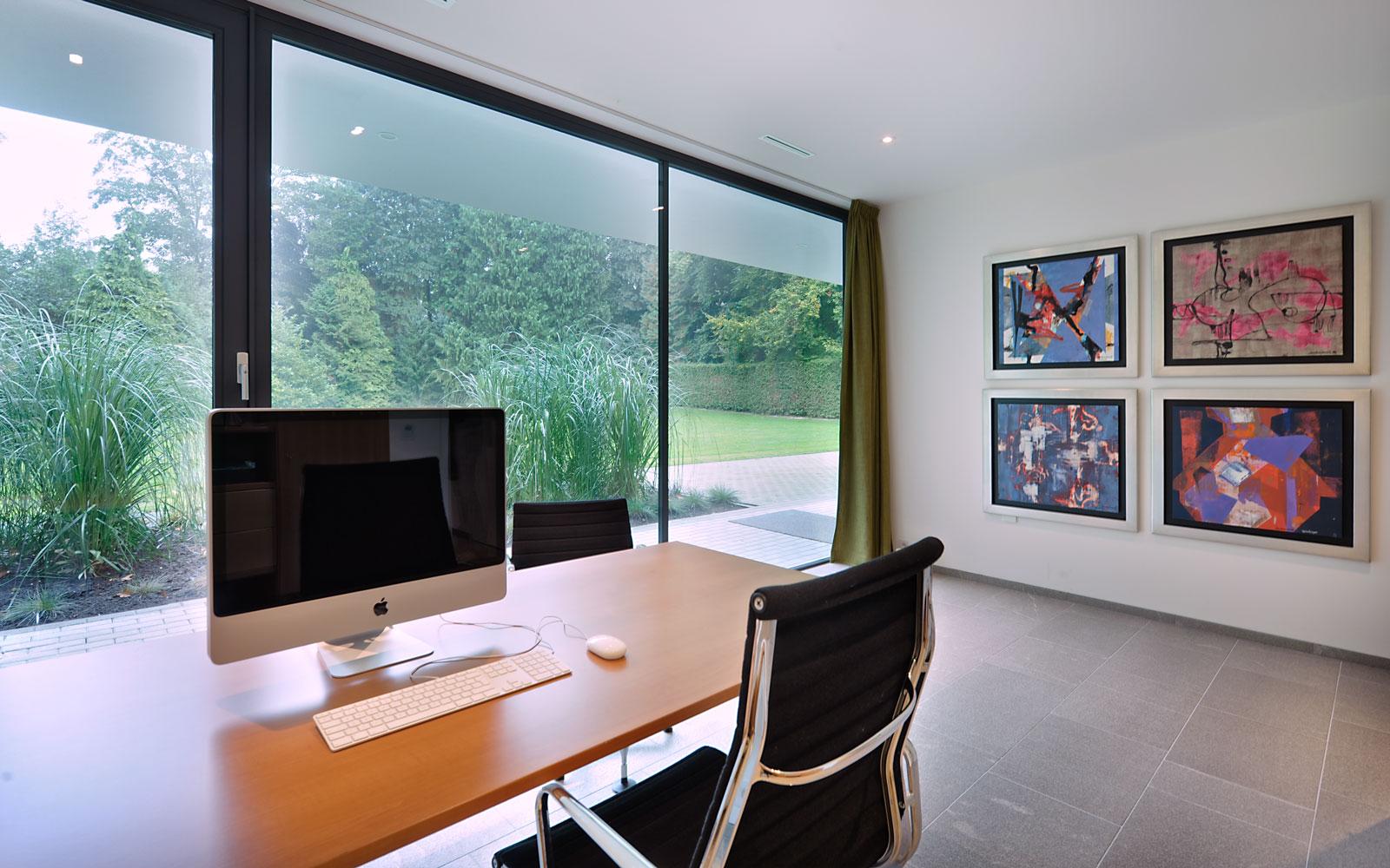 Studeerkamer, bureau, kunst, schilderijen, grote ramen, zicht op de tuin, modern landhuis, Maas Achitecten