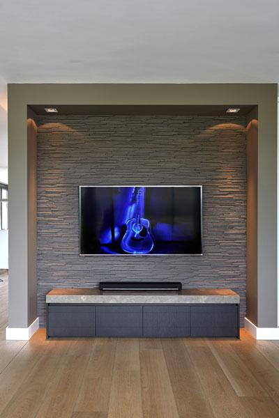 Televisiehoek, televisie, bijzondere muur, stenen muur, donkere kleuren, symmetrische villa, Marco van Veldhuizen