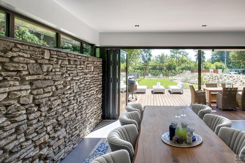 Ruime voortuin, grote ramen, glazen pui, Solarlux, The Flagstone COmpany, natuursteen strips, betonvloer, eettafel, hout, moderne duinvilla, BNLA architecten