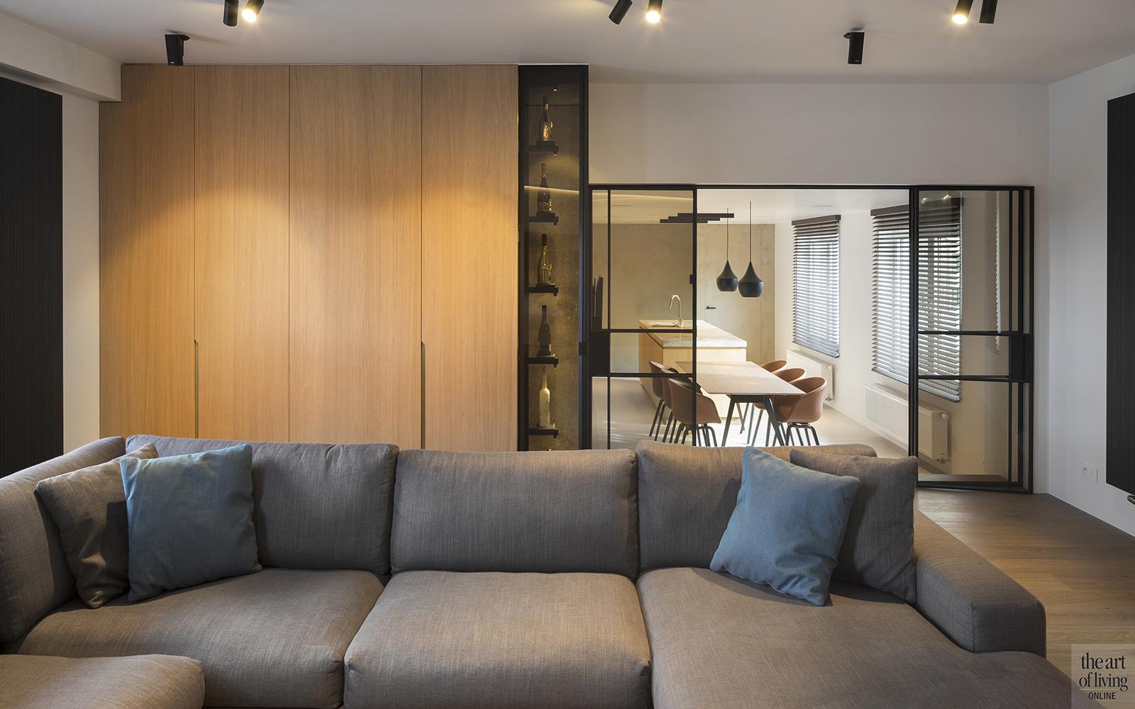 """Penthouse   TDesign Het penthouse met champagne meubel De interieurarchitect voert ook vergaande aanpassingen door in de bouwkundige indeling van een woning. """"Dat moesten we doen in een penthouse in het Waasland. Deze ruimte van om en bij de tweehon- derd vierkante meter woonruimte was zeer onlogisch ingedeeld in het verleden. We hebben gezorgd voor een nieuwe indeling, waarbij het geheel veel opener oogde en compartimenten als die van de slaapkamer en badkamer meer tot hun recht kwamen."""" Diagonale LED lijnen TDesigns zorgde voor een vervanging van de ouderwetse inrichting. Er werd gekozen voor een keur aan natuurlijke materialen, zoals eik neer, Fior Di Bosco marmer, tadelakt en zwart gecoat staal. """"Een stalen deur mét glas geeft een veel mooier effect dan een puur glazen deur"""", legt Seppe Teunen uit. """"Sommige overgangen moet je laten zien, andere moet je juist wegwerken, zoals die voor audio en luchtaanvoer."""" Net als in de modelwoning is de gang meer geworden dan zomaar een corridor die van de ene set kamers naar de andere voert: het is een beleefruimte. LED licht is kunstig weggewerkt in de wanden in de vorm van diagonale lijnen. Dit is een goed voorbeeld van het soort uitdagingen waar TDesigns zijn partners voor plaatst, want de impact van het lichteffect staat of valt met de kwaliteit van de naadloze afwerking. Veel installateurs zouden feestelijk hebben bedankt voor de moeilijkheidsgraad, maar Gepae nam de handschoen op en bracht de opdracht tot een goed einde. Champagnemeubel """"Dit penthouse had een hele tijd leeggestaan en de opdrachtgever twijfelde aanvankelijk erg over mijn plannen met nieuwe indeling, maar gaf me uiteindelijk carte blanche. Ik heb dat vertrouwen niet beschaamd"""", stelt Seppe Teunen. Uit het bevragen naar het leefpatroon kwam als één van de antwoorden naar voren dat de eigenaar een echte liefhebber van de betere champagne is. Een plek in huis om in ieder geval een aantal van die flessen te bewaren en te tonen was welkom. """"We hebben daarop ee"""